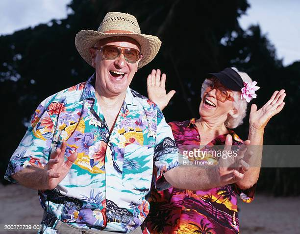 Mature couple in Hawaiian shirts gesturing with hands, portrait