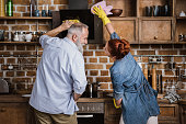 Back view of mature couple having fun while cleaning kitchen appliances