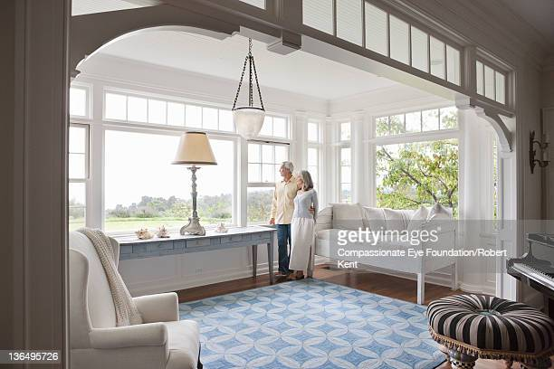 Mature couple in living room looking out of window
