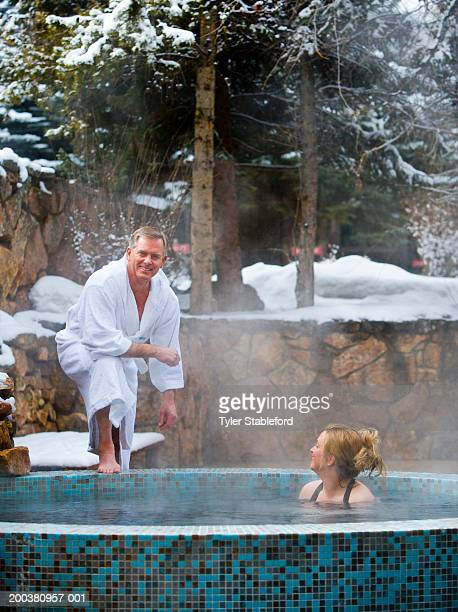Mature couple in outdoor hot tub on snow day, portrait