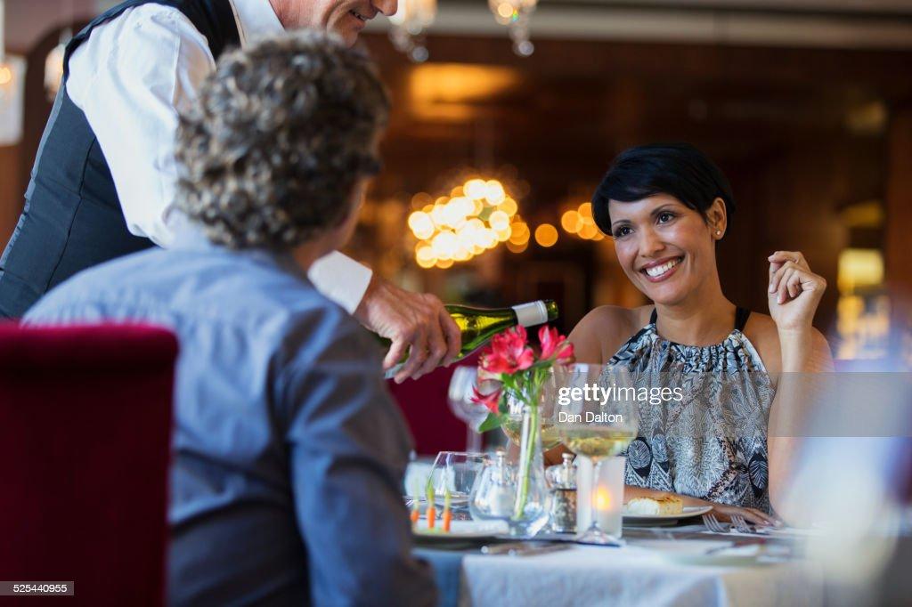 Mature couple in restaurant, waiter pouring white wine : Photo