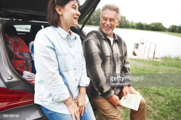 Mature couple in rural setting, standing beside car, laughing