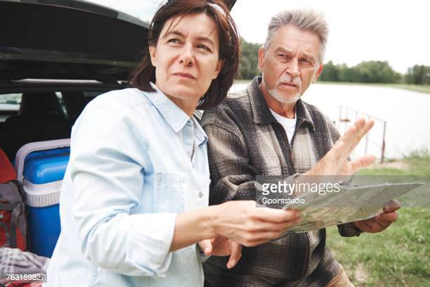 Mature couple in rural setting, standing beside car, looking at map