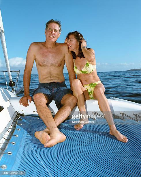Mature couple in swimsuits sitting on boat