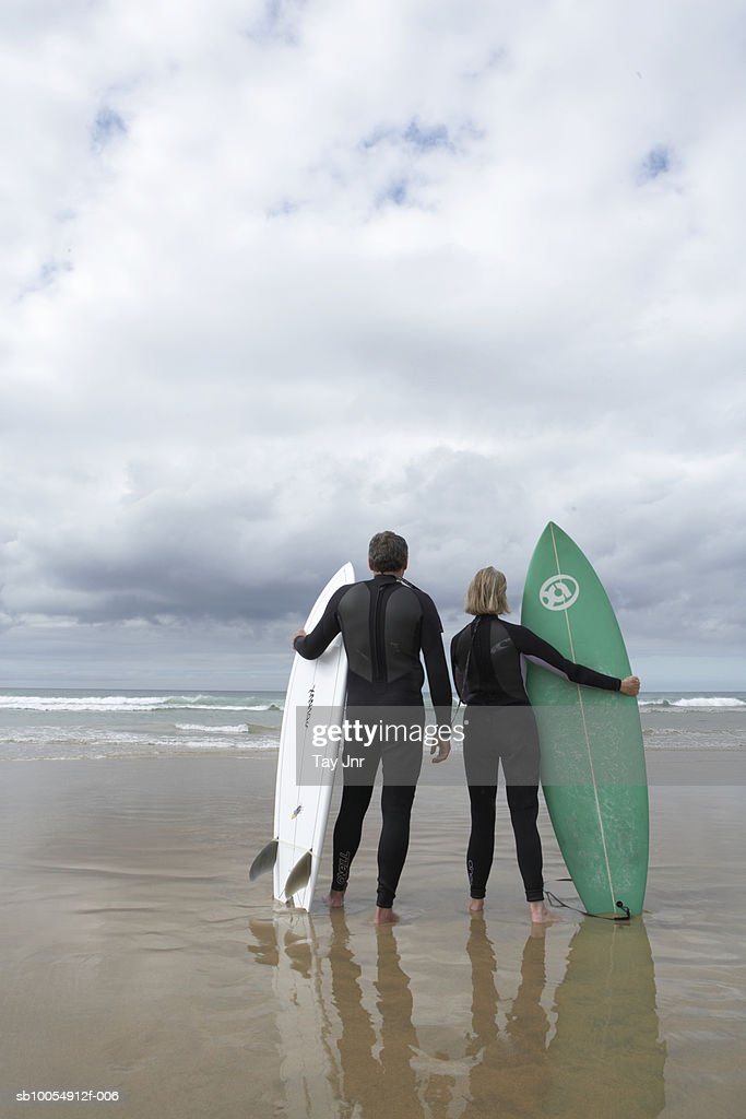 Mature couple in wetsuits standing on beach at edge of sea, holding surfboards, rear view : Stock Photo