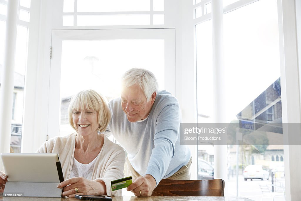 Mature couple internet shopping in a cafe : Stock Photo