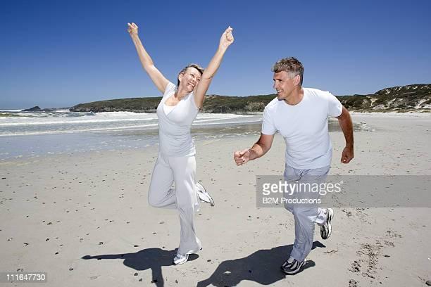 Mature couple jogging on beach
