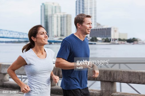 Mature couple jogging together along waterfront