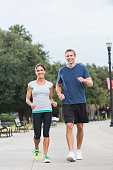 Front view of mature couple jogging or power walking together along a pedestrian walkway in a park.