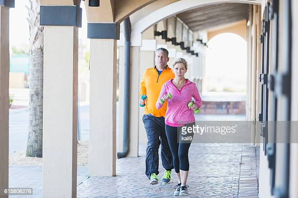 Mature couple jogging with hand weights