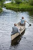 Mature couple kayaking, rear view