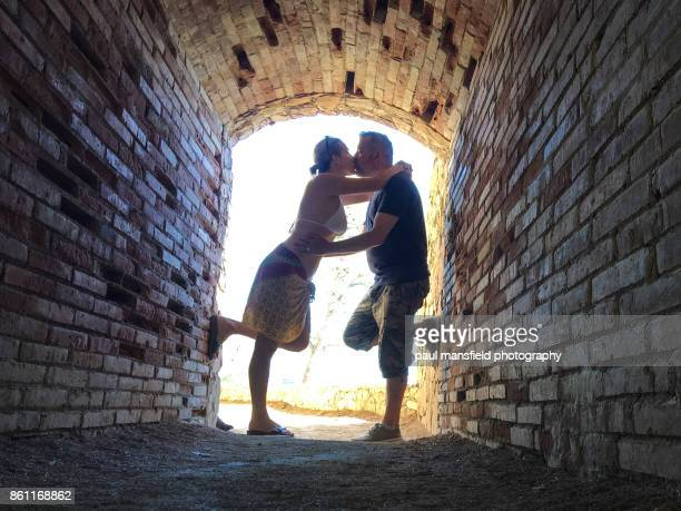 Mature couple kissing in small tunnel