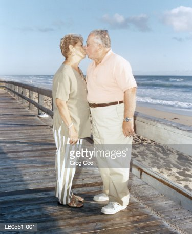Mature couple kissing on boardwalk : Stock Photo