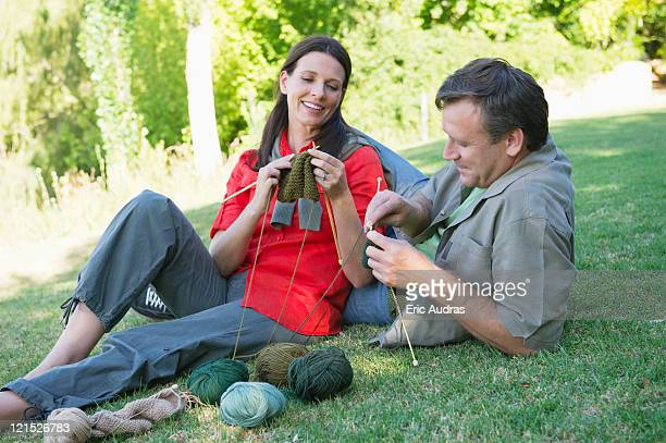 Mature couple knitting together in the garden