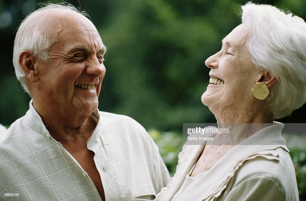 Mature couple laughing outdoors : Stock Photo