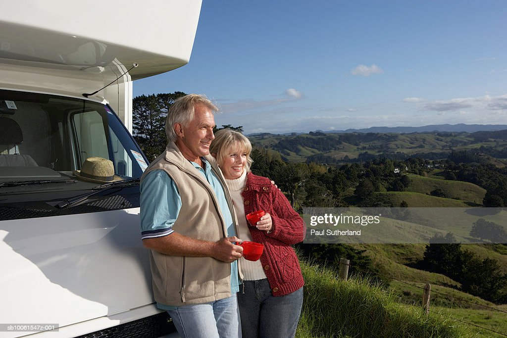 Mature couple leaning on motor home, drinking tea and looking at landscape
