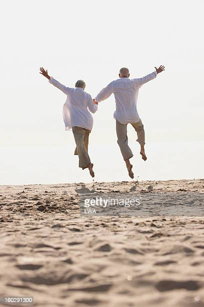 Mature couple leaping into air