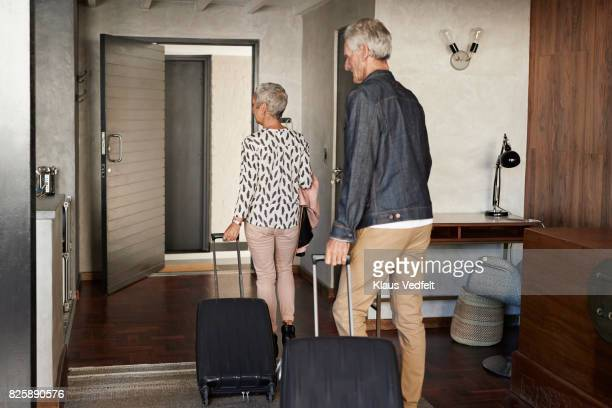 Mature couple leaving rental flat, with suitcases and bag