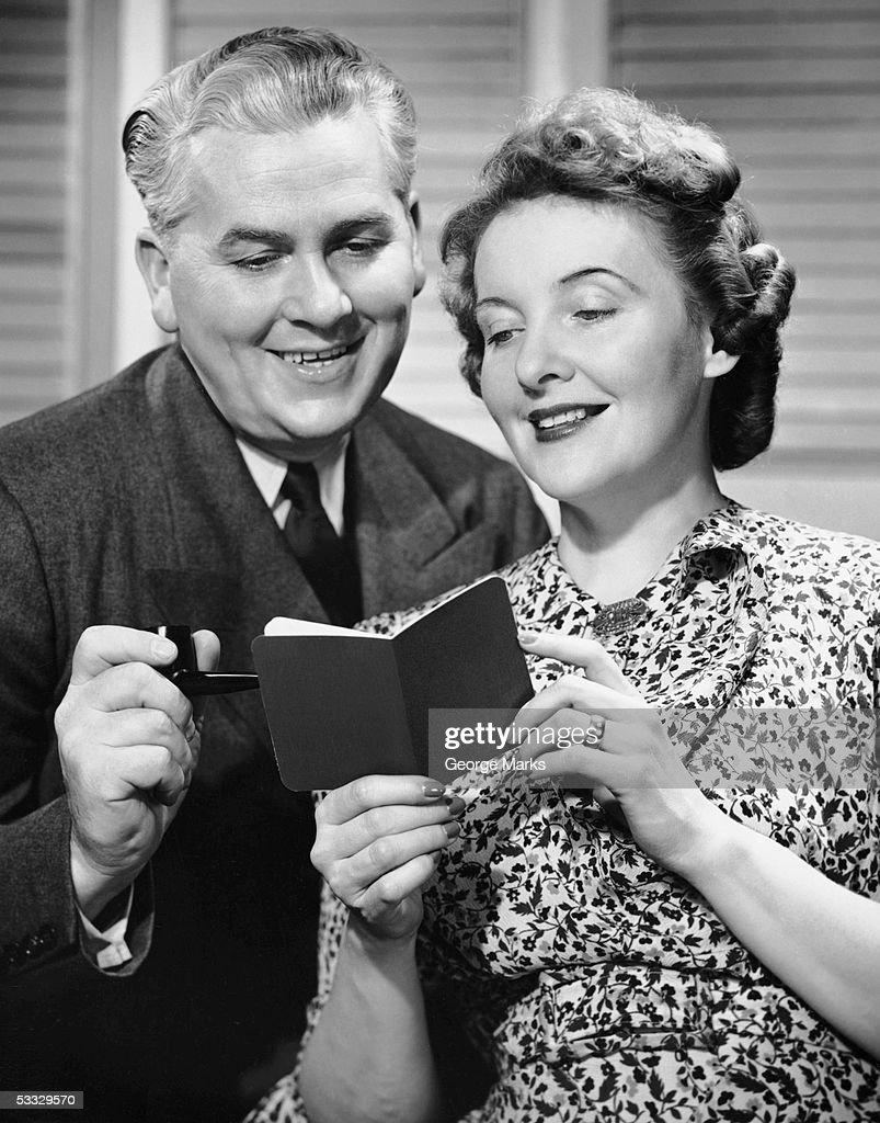 Mature couple looking at bank book : Stock Photo