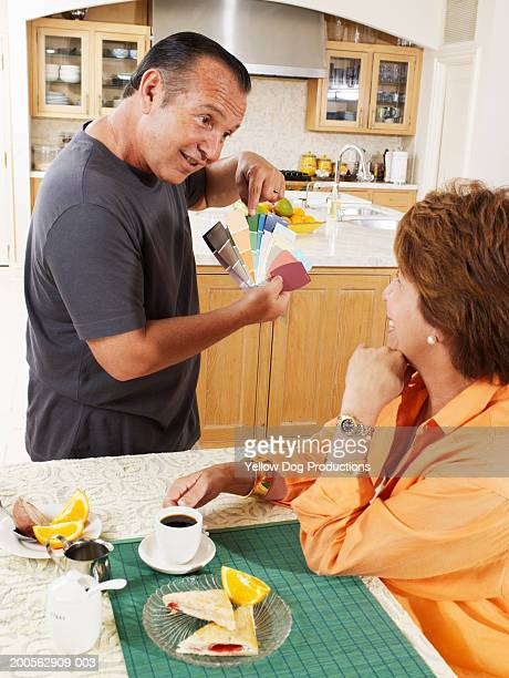 Mature couple looking at colour samples in kitchen