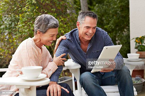 Mature couple looking at digital tablet in garden