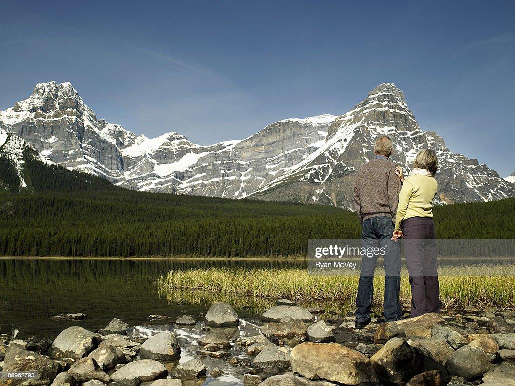 Mature couple looking at mountain range : Stock Photo