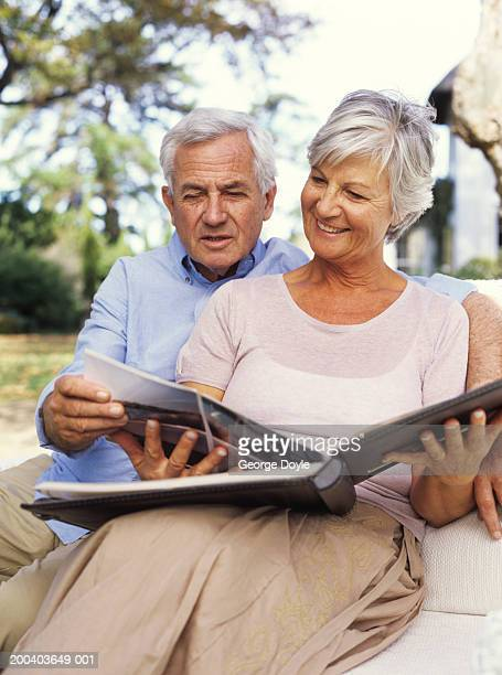 Mature couple looking at photo album, smiling