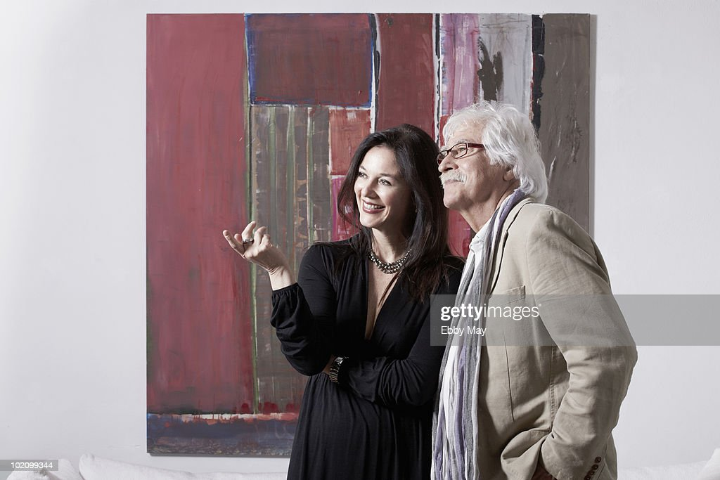 Mature couple  looking at pictures in art gallery : Stock Photo