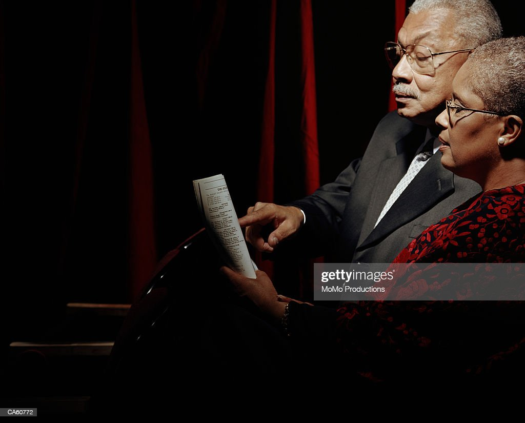 Mature couple looking at program in opera house