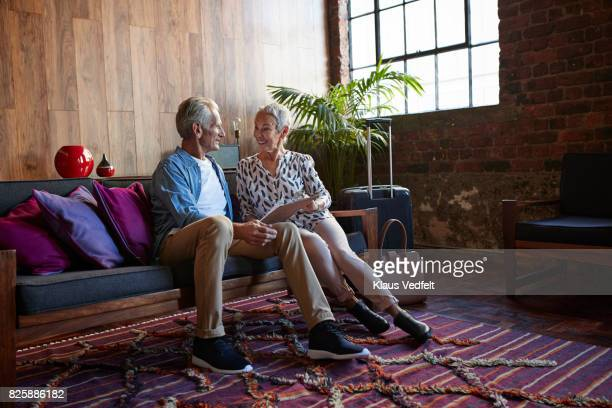 Mature couple looking threw tjeck-in clip board, after arrival in rental flat