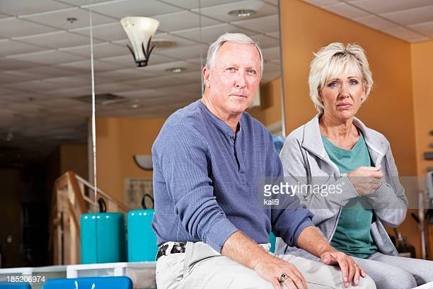Mature couple looking worried in physical therapy clinic