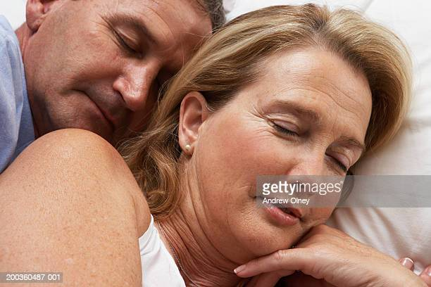 Mature couple lying in bed, eyes closed, close-up