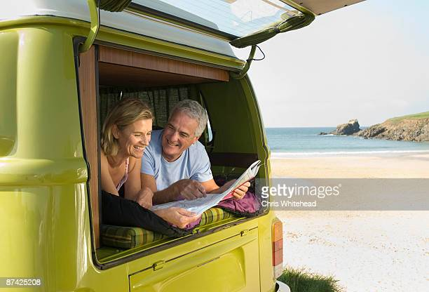 Mature couple lying in camper van