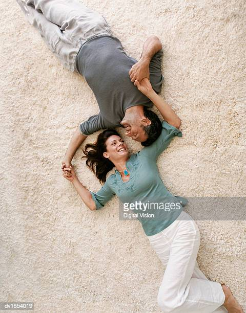 Mature Couple Lying on a Carpet Holding Hands, Viewed From Directly Above