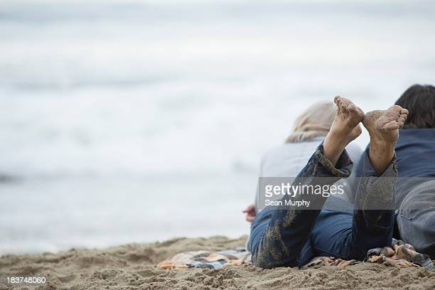 Mature couple lying on beach looking at sea