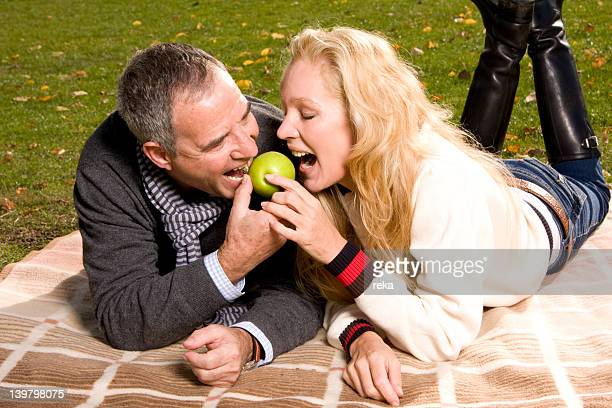 Mature couple lying on blanket sharing an apple