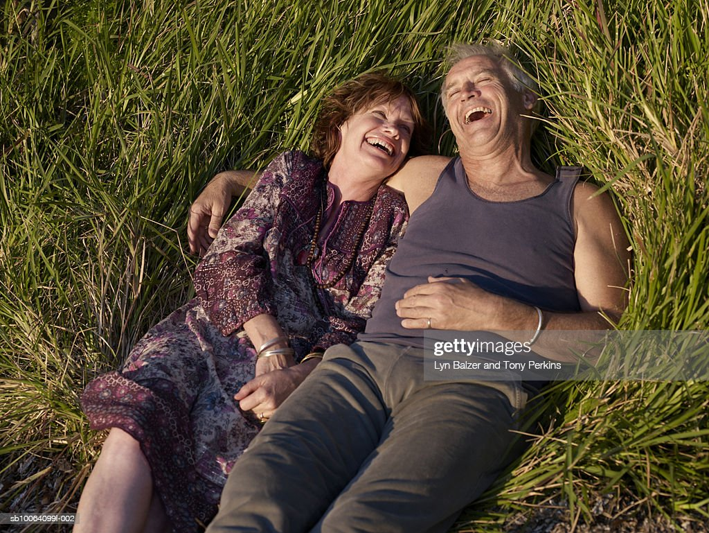 Mature couple lying on grass, elevated view : Stock Photo