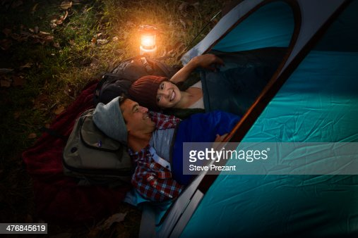 Mature couple lying together in tent : Stock Photo