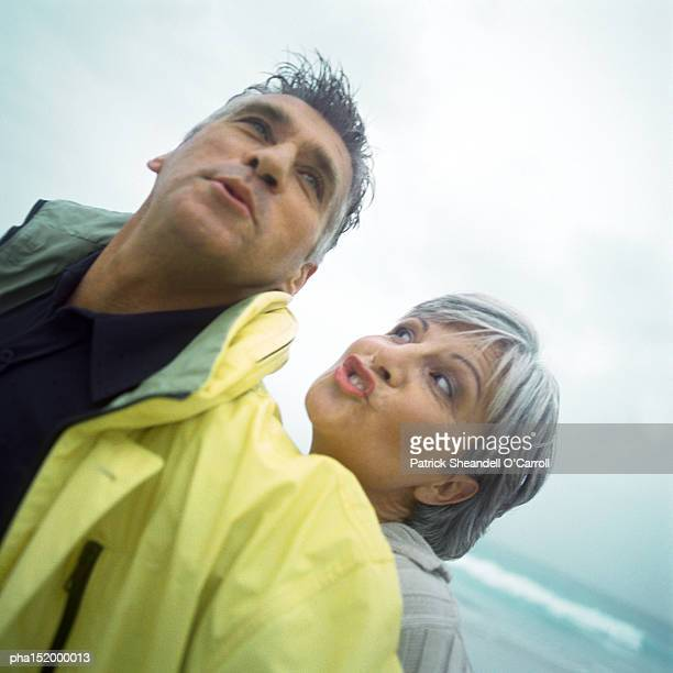 Mature couple making faces on beach, portrait.
