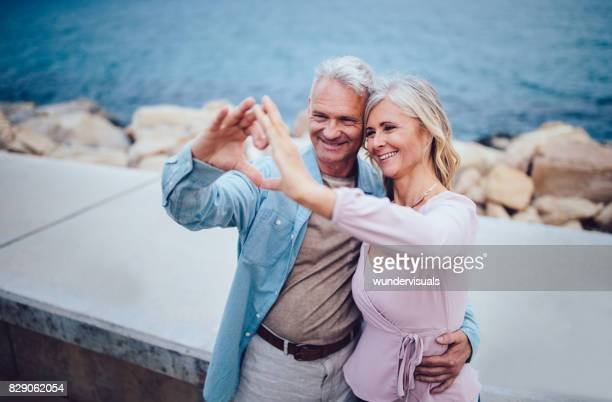 Mature couple making heart shape with their hands at seaside