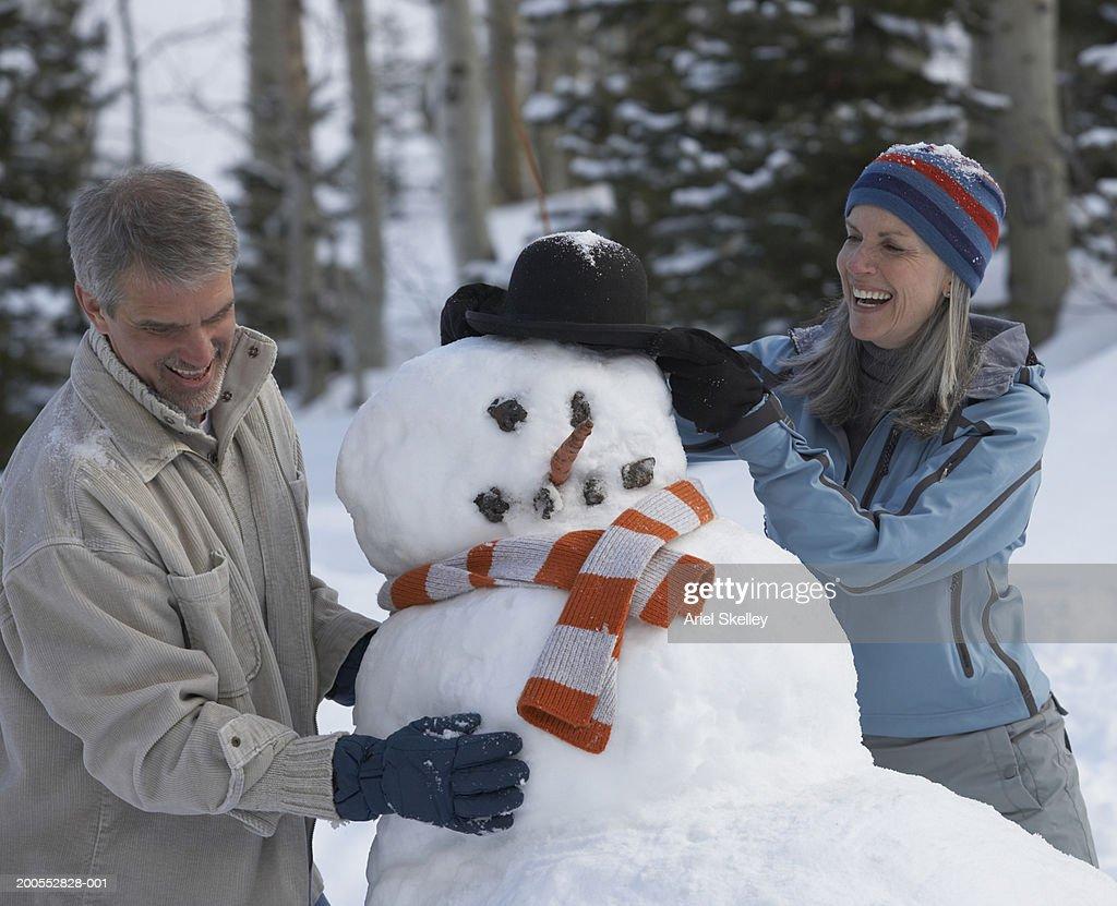 Mature couple making snowman, smiling : Stock Photo
