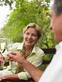 Mature couple making toast, focus on woman smiling, portrait
