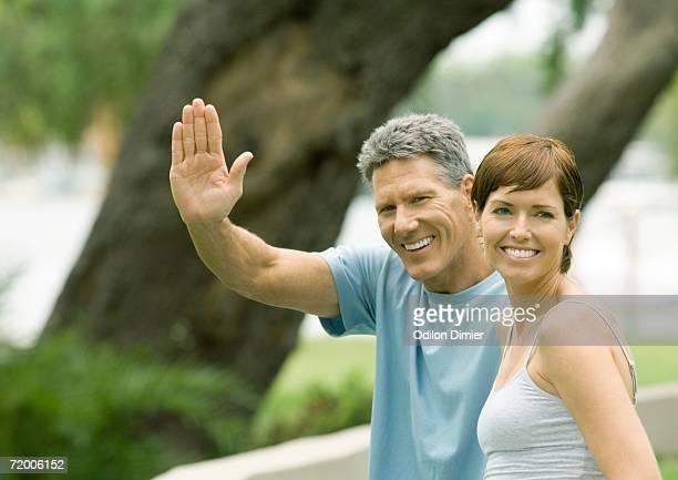 Mature couple, man waving