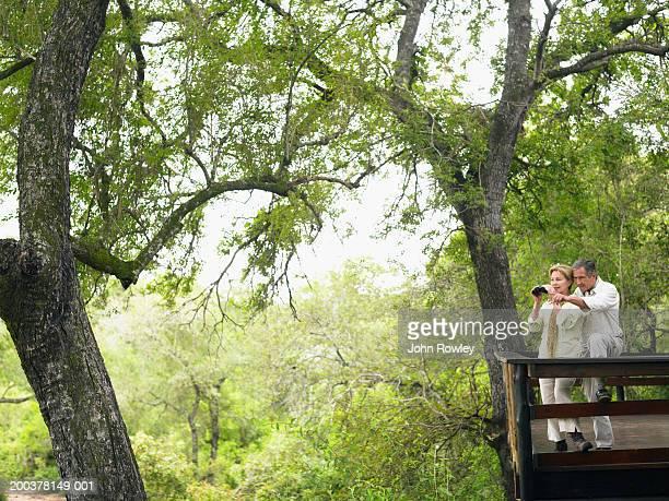 Mature couple on balcony of lodge, woman holding binoculars