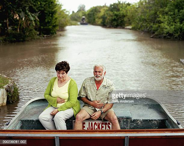 Mature couple on boat holding stomachs