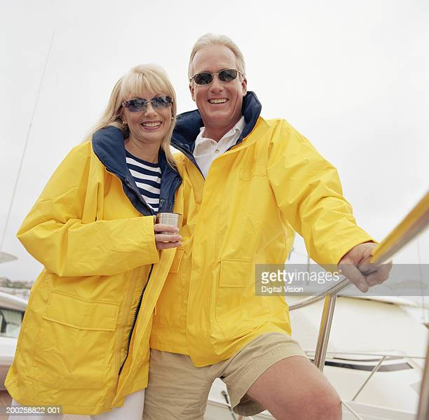 Mature couple on boat, wearing rain jackets and sunglasses, smiling