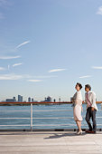 Mature couple on deck of cruise ship, skyline in background, side view