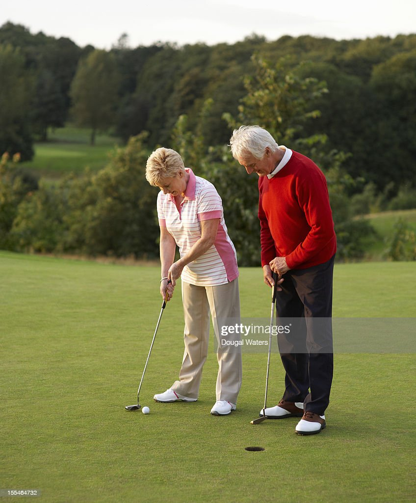 Mature couple on golf green preparing to putt ball : Stock Photo