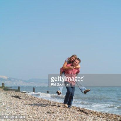 Mature couple on pebble beach, man giving woman piggyback : Stock Photo