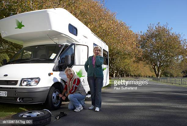 Mature couple on road, man changing tire in motor home, woman using mobile phone